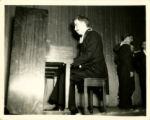 Photograph of St. John's College students at piano and singing in a variety show