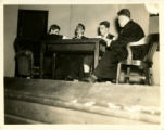 Photograph of four St. John's College students sitting at table on stage in a variety show