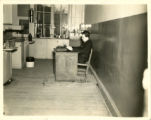Photograph of a St. John's college professor at desk in a chemistry classroom